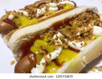Two hot dogs with tomato, mustard, mayonnaise and fried onion