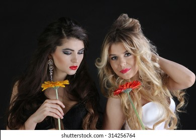 Two hot sexy female in lingerie with flowers on black background