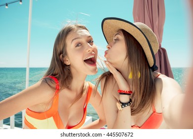 two hot smiling young women on beach making selfie