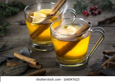 Two hot  whiskey, rum, apple or brandy toddy cocktail drinks with cinnamon set on rustic wood