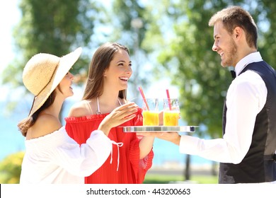 Two hotel customers on summer vacations and a waiter serving them drinks with the ocean in the background