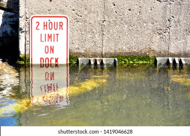 Two hour limit on dock sign showing the record high water levels of Lake Michigan and the Great lakes in spring.