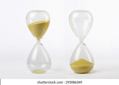 two hourglasses with yellow sand: from start to the end on white background