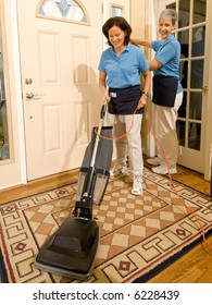 Two house keeping maids working in a high end entry way to a residential home. One made using a vacuum cleaner.