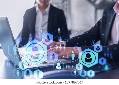 Two HR specialists in formal wear analyzing the recruitment market using laptop to boost the intern program at international consulting company. Social networking hologram icons. - Shutterstock ID 1897867567