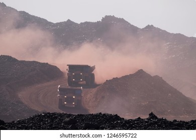two huge tucks in a ore daylight mining in africa