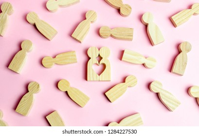 Two human figures together form a void in the shape of a heart on a pink background. Concept of love and search for the second half. Find a soul mate and start a family. Love and romance