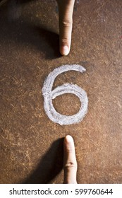 two human fingers arguing whether a number on the floor is a 6 or a 9. Concept of ideological perspective.