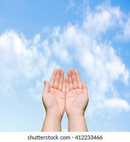 two human hands against the blue sky