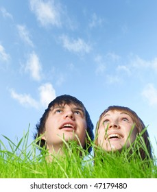 Two human heads stick out from green grass on blue sky background
