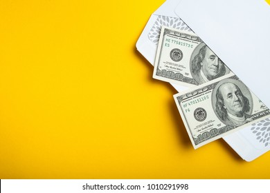 Two hundred dollars in an envelope on a yellow background, empty space for text.