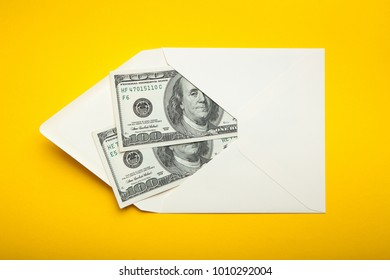 Two hundred dollars in an envelope on a yellow background, corruption.