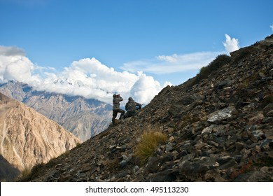 Two hunters in camouflage clothing with a gun on the mountain side in the Tian-Shan, Kyrgyzstan;
