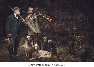 Two hunters with dogs and shotguns in a traditional shooting clothing on a dark forest background.