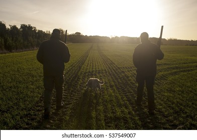 Two hunters and a hunting dog on a field