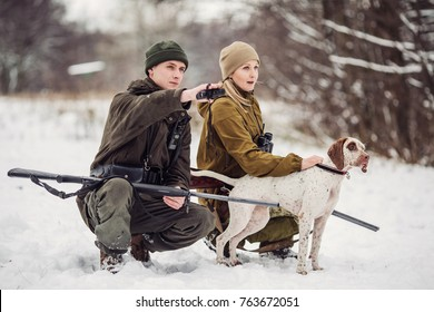 two hunters with rifles in a snowy winter forest. hunting concept