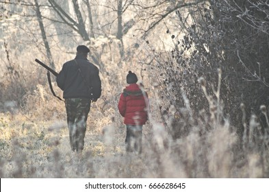 Two hunters at sunrise. Hunter man and boy during hunting period in search of wildfowl or game. Autumn hunting season. Grandfather teaches his grandson the hunting craft