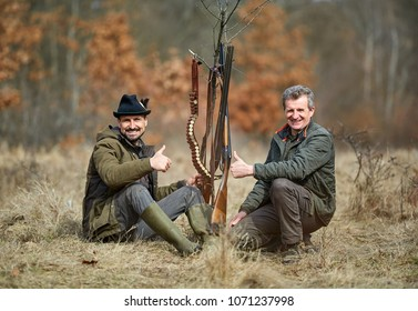 Two hunters together in the forest with double barrel guns