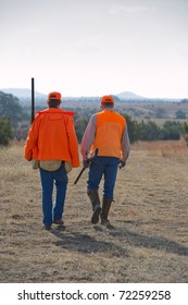 two hunters walking in a field