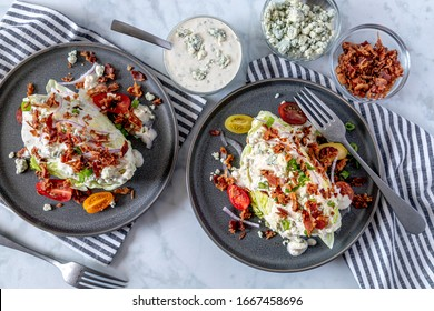 Two ice berg lettuce wedge salads with blue cheese dressing, bacon, tomatoes, onions, chives sitting on gray stoneware plates shot from above. Surrounded by ingredients. Keto.