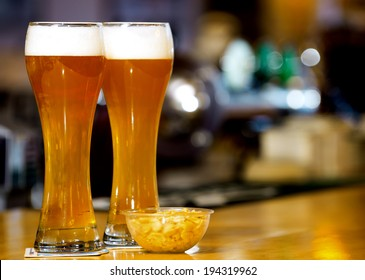 two ice cold glass of beer and bowl of peanuts standing on wooden counter at a bar / two glasses of beer