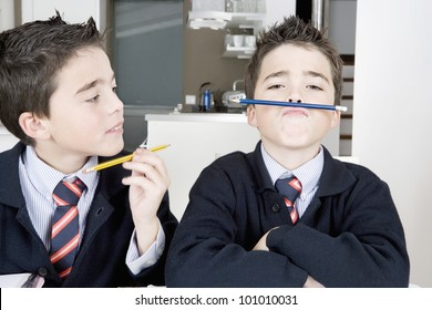 Two identical twin brothers doing their homework on the kitchen table and getting distracted with games.