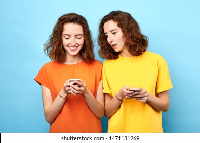 two identical twins holding mobile phones, making a phone call, playing online games, surfing, browsing the net . isolated blue background, studio shot