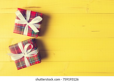 Two identical wrapped gift boxes over yellow wooden planks