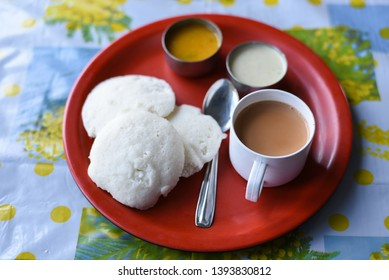 Two Idli or idly with coconut chutney and sambhar and Indian milk tea. popular breakfast of South India and Sri Lanka. Healthy steamed cakes made by steaming fermented batter of black lentils, rice