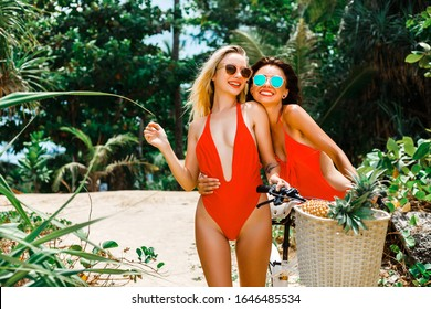 Two incredible beautiful sexy ladies in red bikini and sunglasses on a tropical island. Bike cruiser. Travel and vacation summer mood, enjoyment and happiness