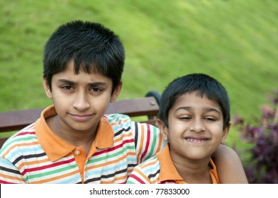 Two Indian brothers sitting happily at a local park