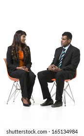 Two Indian Business People sitting down having a meeting. Indian man and woman business partners. isolated on a white background.