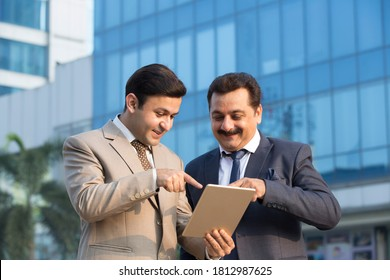 Two Indian businessmen using digital tablet outdoors in city