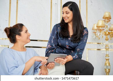 Two Indian businesswomen sitting on sofa using digital tablet and discussing online presentation together at luxury office