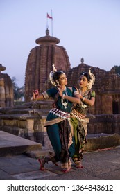 Two Indian classical odissi dancers striking a pose in front of Mukteshvara Temple,Bhubaneswar, Odisha, India