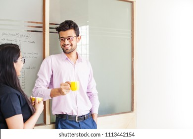 Two indian colleagues talking over cup of coffee
