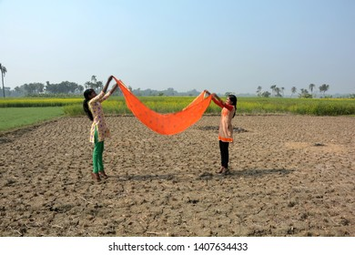 Two Indian Girls wearing traditional colorful salwar kameez flying their urna/cloth in field with blue sky and mustard/rapeseed flowers in the background,enjoying and cheerful mood. Selective focusing