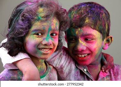 Two Indian kids with face smeared with colors. Concept for Indian festival Holi.
