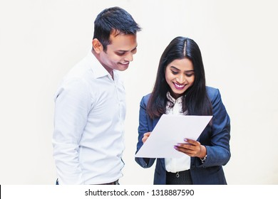 Two indian office colleagues discussing a document on white background