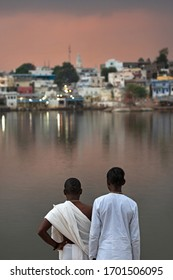 Two Indian people (Brahmans) looking over the holy city of Pushkar -India (focus on people, city/background slightly blurred)