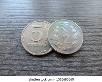 The two indian rupees coin laying over 5 Russian rubles coin, the indian rupees have an advantage and are bigger