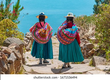 Two indigenous Quechua women in traditional clothes walking down the path to the harbor of Isla Taquile (Taquile Island) with the Titicaca Lake in the background, Peru.