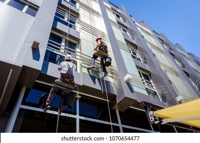 Two industrial climbers are washing, cleaning facade of a modern office building