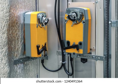 Two industrial orange damper actuators installed on the air handling unit