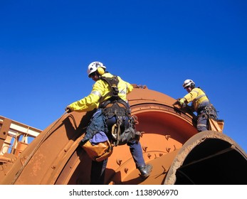 Two industrial rope access fitters, boiler maker wearing safety harness using twin rope hanging working fasten a bolts with rattle gun top of the chute as fall arrest position construction mining site