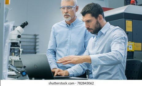 Two Industrial Scientists/ Engineers/ Technologists Have Discussion while Working on Laptop Computer. In the Background Modern Laboratory/ Factory Equipment.