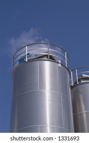 Two industrial stainless steel tanks against blue sky with white clouds