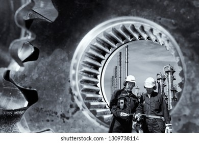 two industry workers in front of giant gears machinery