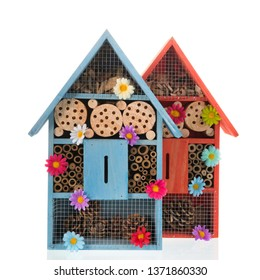 Two insect hotels with flowers isolated over white background