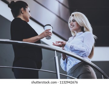 Two Interesting Businesswomen on Coffee Break. Meeting Outside Office. Beautiful Cute Smiling Women. Young Smart Female Partners Talking about Documents. Hardworking together. Teambuilding.